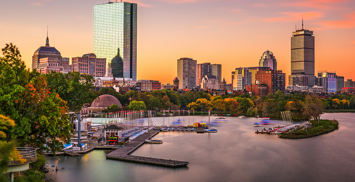 A view of the Boston skyline over Boston Harbor at sunset.