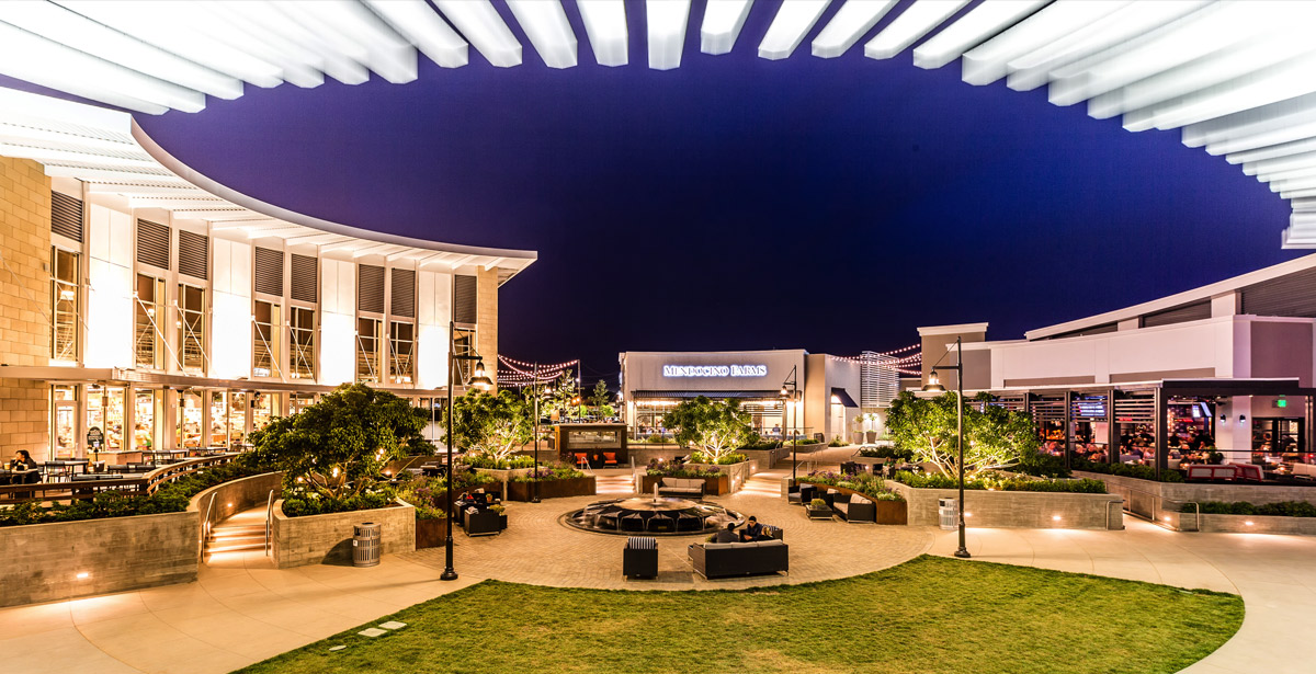 An outdoor kinetic structure with a sitting area at a recently-developed Regency center.