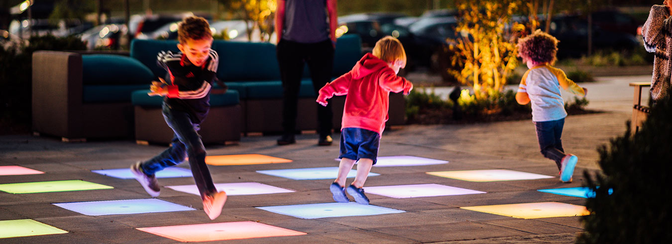 Children playing on lighted floor at shopping center.