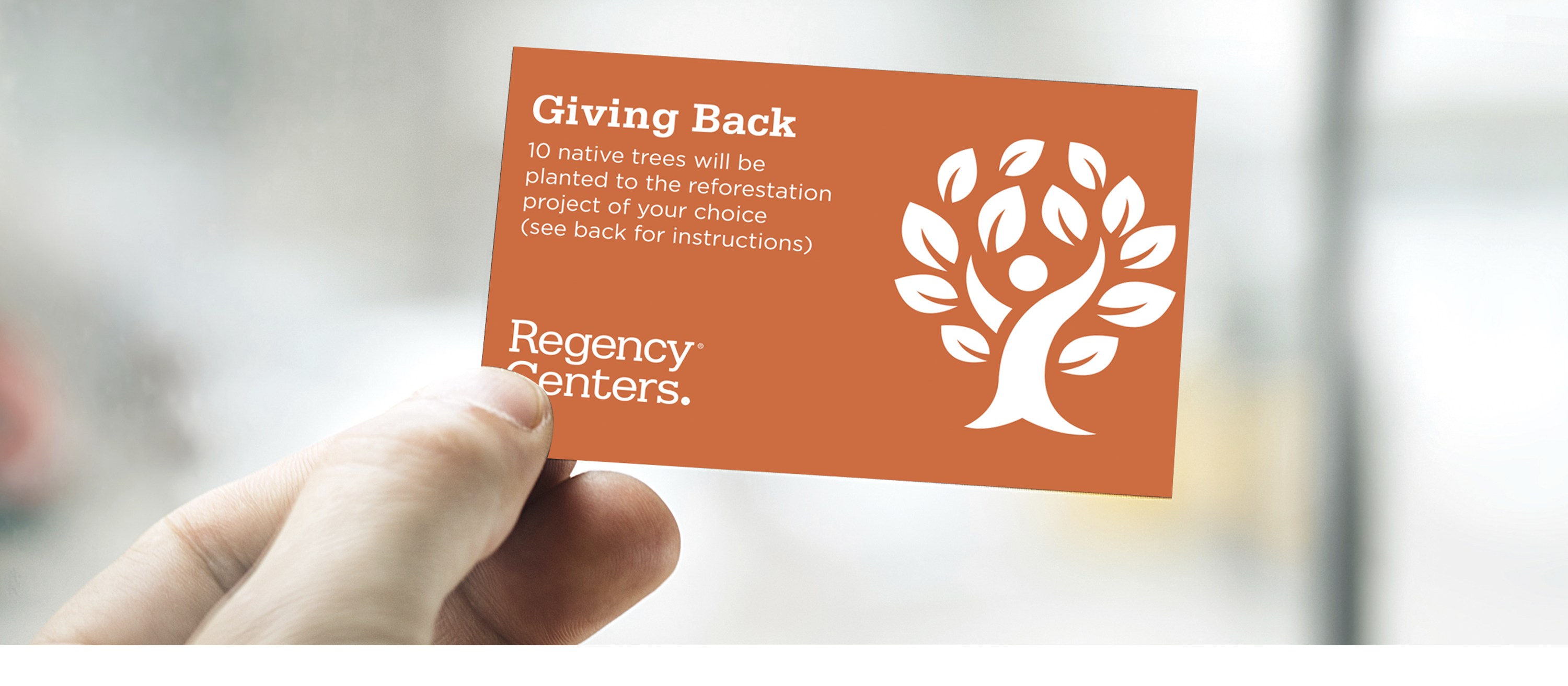 Image of hand holding card with text printed on it: Giving Back. 10 Native trees will be planted to the reforestation project of your choice (see back for instructions). Regency Centers
