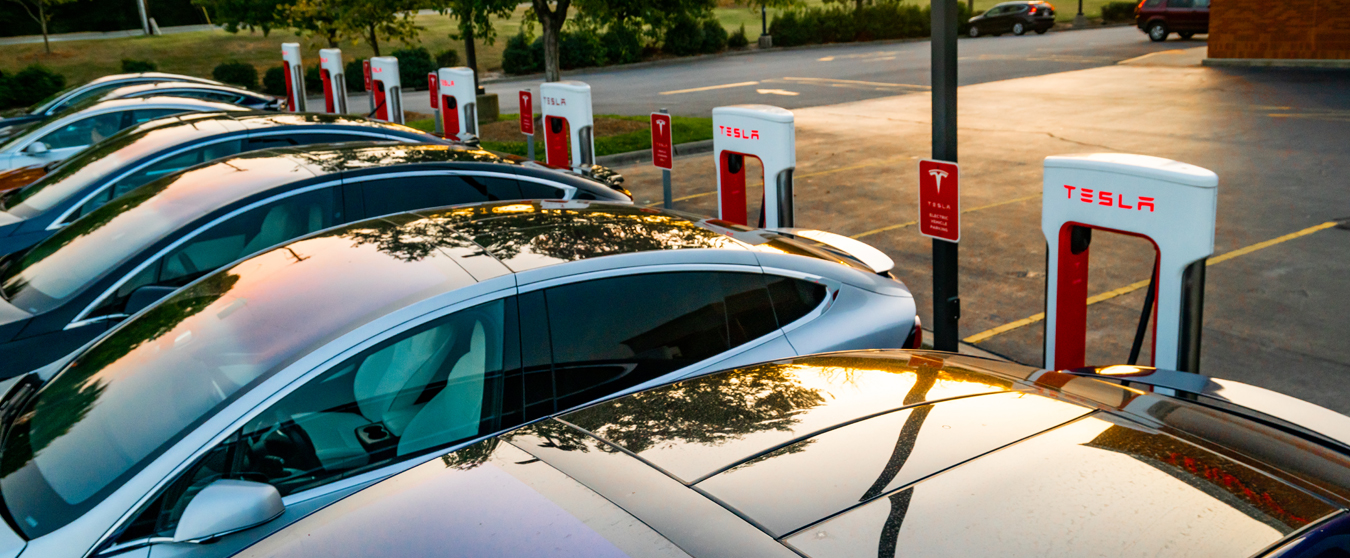 Photo of Tesla vehicle recharging station with cars parked and charging