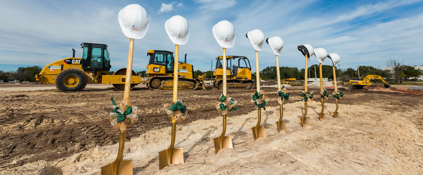 Photograph of ground breaking ceremony set up with heavy machinery in background and shovels with hard hats in the foreground