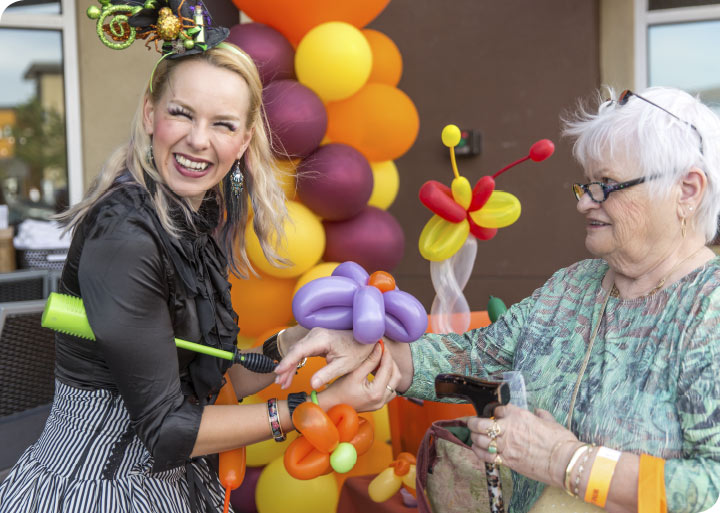 A young woman dressed in costume and making balloon animals puts a balloon flower on another woman's wrist while smiling for the camera.