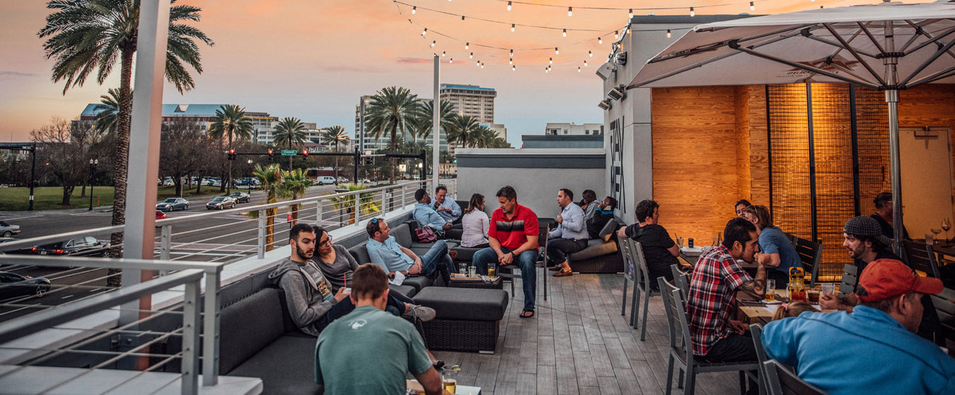 Groups of people eating and having beverages on a rooftop patio.