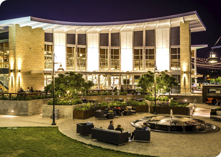 Outdoors at one of Regency's signature centers, with impressive lit columns and a fountain, surrounded by greenery and people sitting on outdoor lounge furniture.